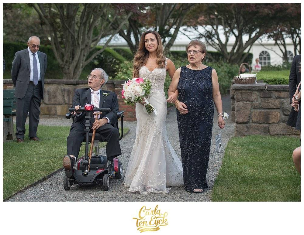 Bride in Eve of Milady wedding gown walks down aisle with dad in wheelchair at Mansion at Turner Hill Ipswich MA