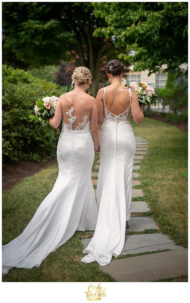 Two brides in Pronovias and Enzoani wedding gowns walk to their wedding at Jonathan Edwards Winery North Stonington CT