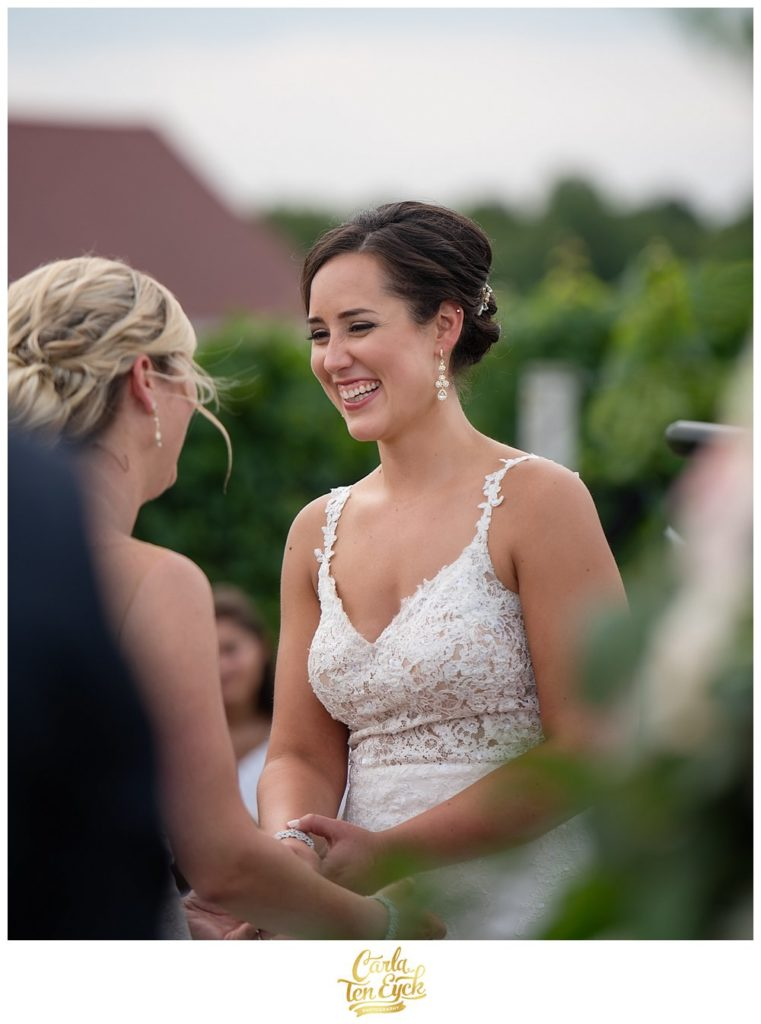 Two brides laugh at their wedding ceremony at Jonathan Edwards Winery North Stonington CT