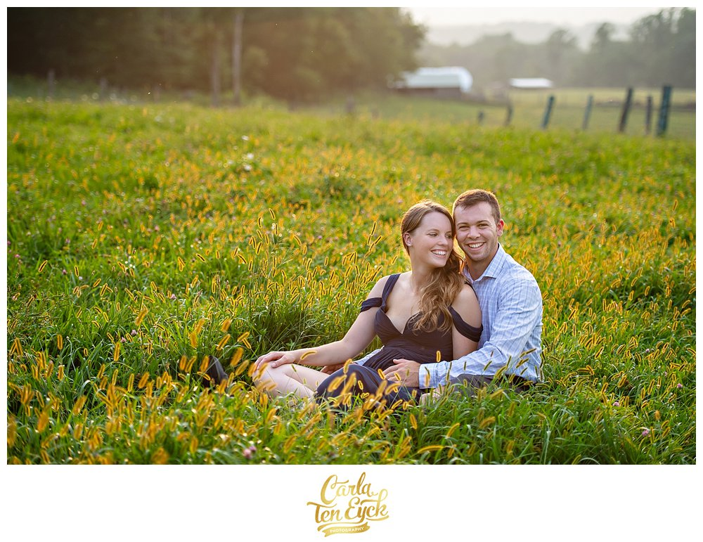 Happy couple in a field at sunset at their engagement session at Heritage Homestead in Northford CT