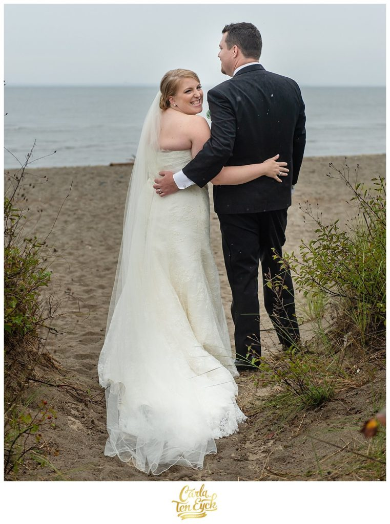 Happy bride and groom on the beach in the rain at their wedding in Lordship CT
