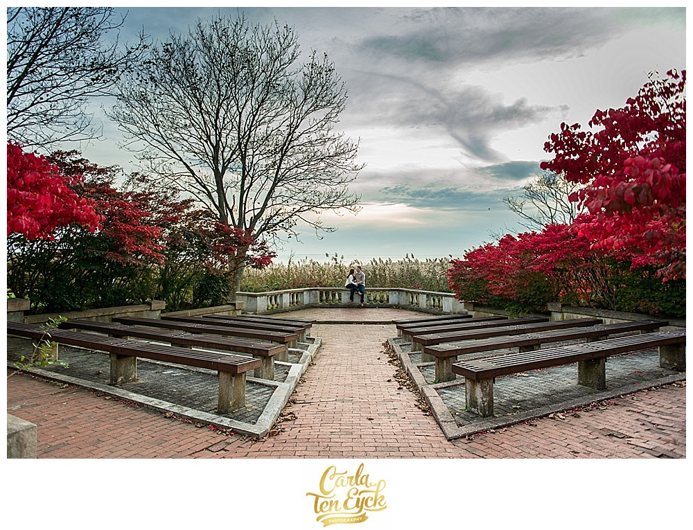 Couple sits in the amphitheater at their engagement session at Harkness Memorial Park in Waterford CT