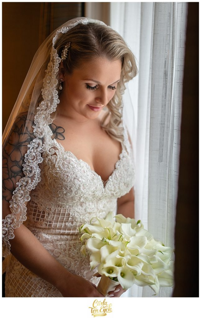 Bride in Stella York wedding gown looks at her calla lily wedding bouquet at the Aria in Prospect CT