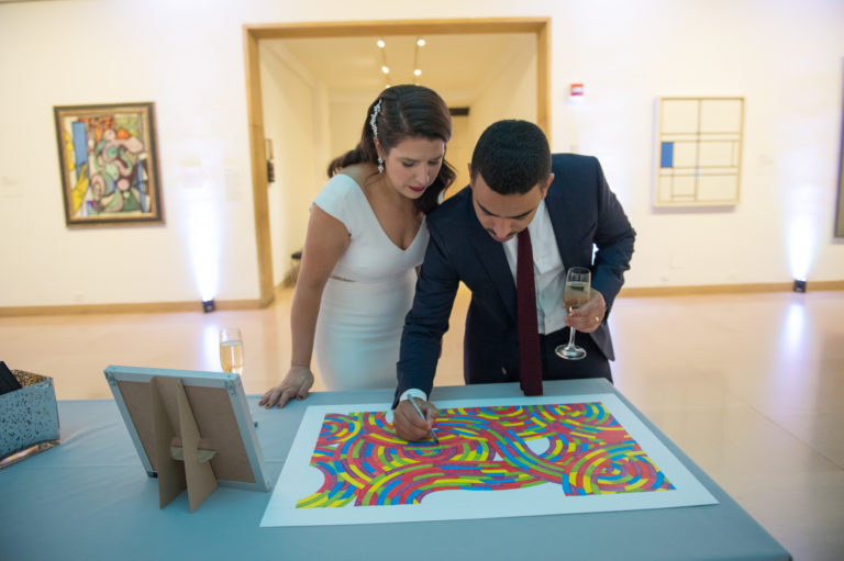 Couple signs their guest book at their wedding at Wadsworth Atheneum in Hartford CT