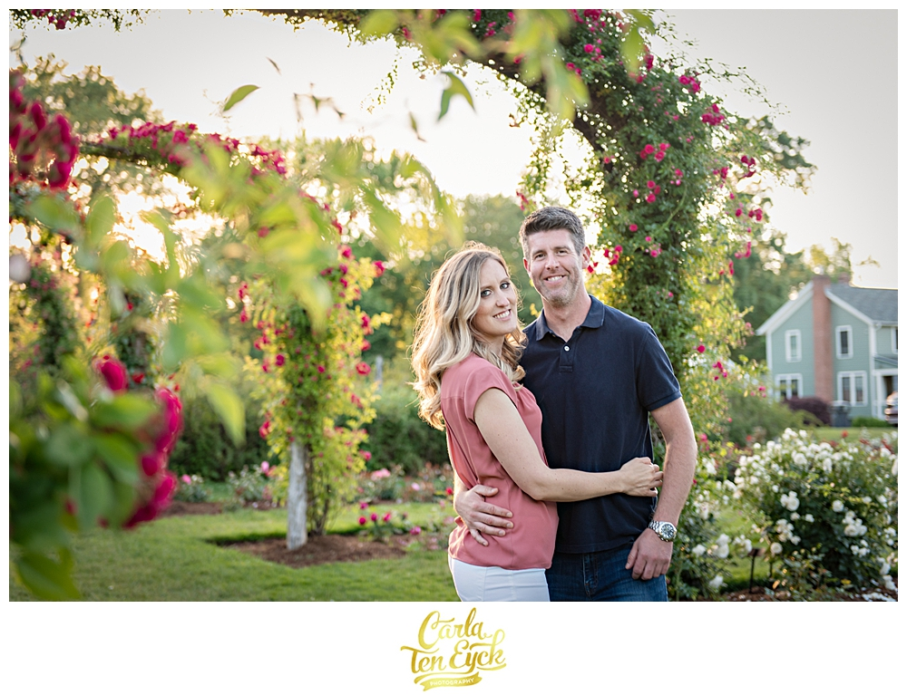 Couple smiles under the rose arches in the rose garden in Hartford CT at Elizabeth Park