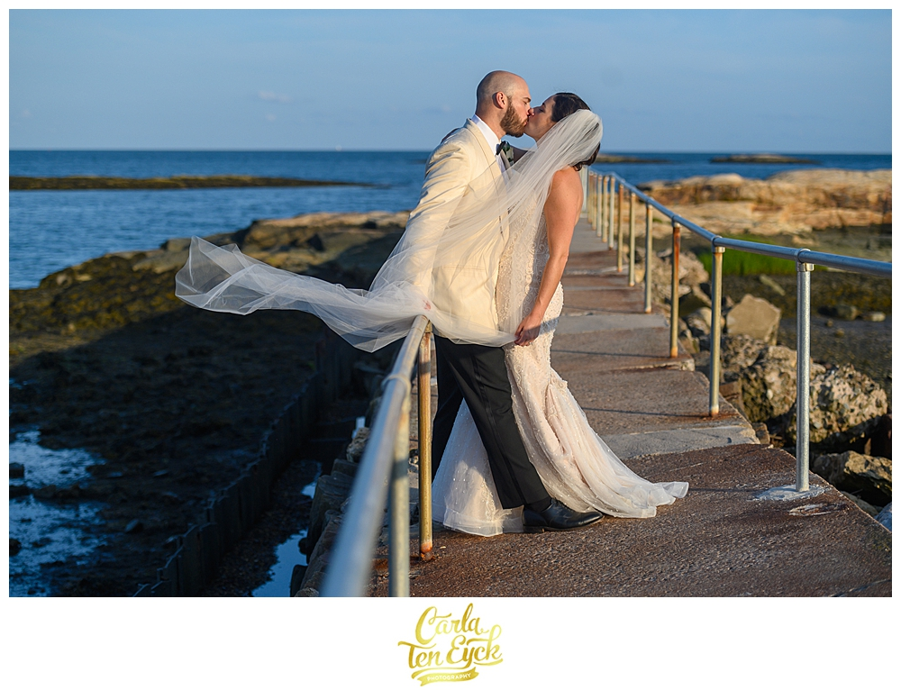 Bride and groom kiss on the rocks at their wedding at The Owenego Inn in Branford CT