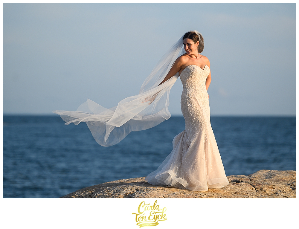 Bride lets her veil blow in the wind on the rocks at her wedding at The Owenego Inn in Branford CT