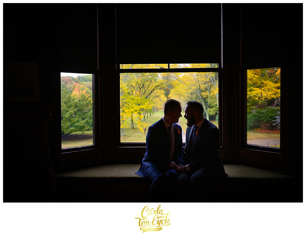Two grooms snuggle at their wedding at the Eustis Estate in Milton MA