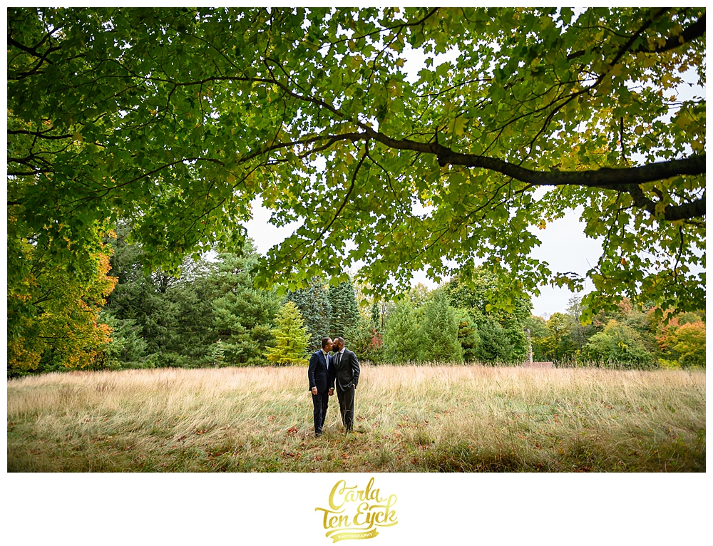 Two grooms kiss under a tree at their wedding at the Eustis Estate in Milton MA