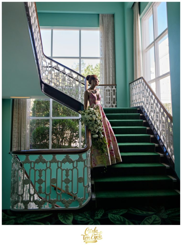 A bride poses on the colorful stairway at The Greenbrier in West Virginia