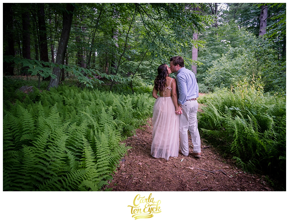 A couple kisses in the ferns during their micro wedding during covid 19