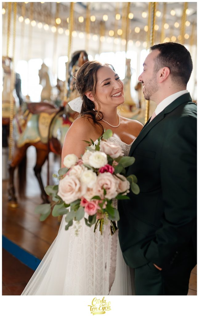 A bride and groom pose for photos at their wedding at Lighthouse Point Park in New Haven CT in the carousel