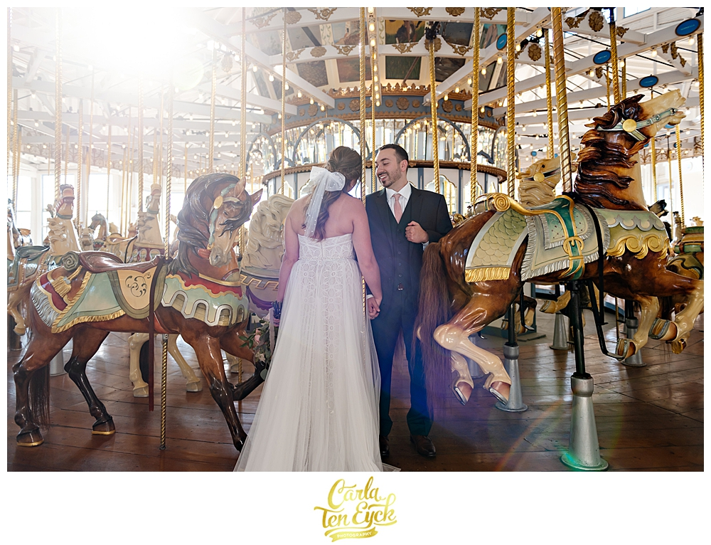 A bride and groom pose for photos on the carousel at their wedding at Lighthouse Point Park in New Haven CT