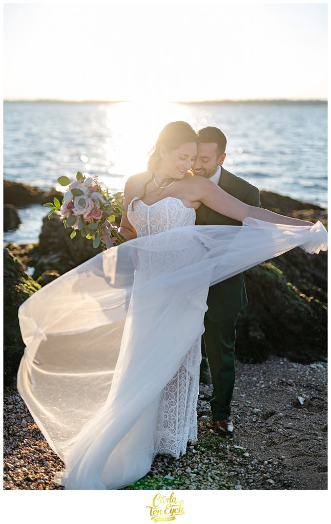 A bride and groom pose for pictures on the beach after their wedding at Lighthouse Point Park in New Haven CT