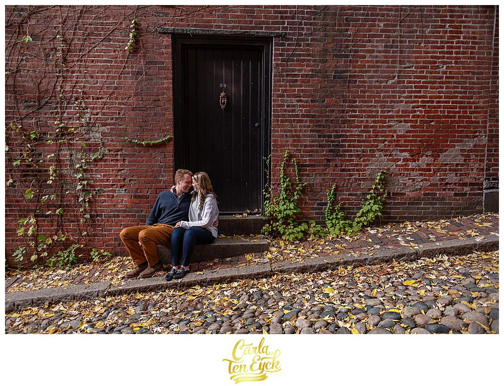 A couple snuggles on Acorn Street during their Boston Engagement session.