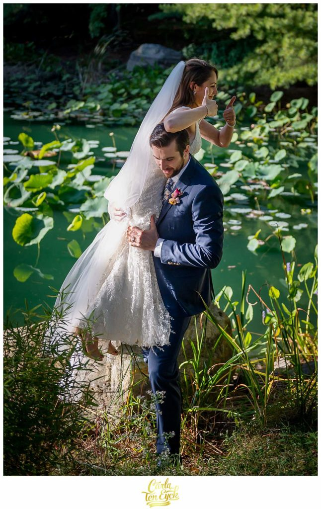 A groom picks up his bride by the lily pond at their wedding at Chatfield Hollow Inn in Killingworth CT