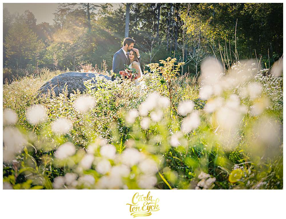 A bride and groom embrace in a field during their intimate wedding at The Chatfield Hollow Inn in Killingworth CT