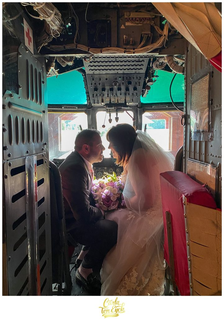 A couple poses in the coast guard helicopter in the helicopter suite at their Winvian wedding in Morris CT