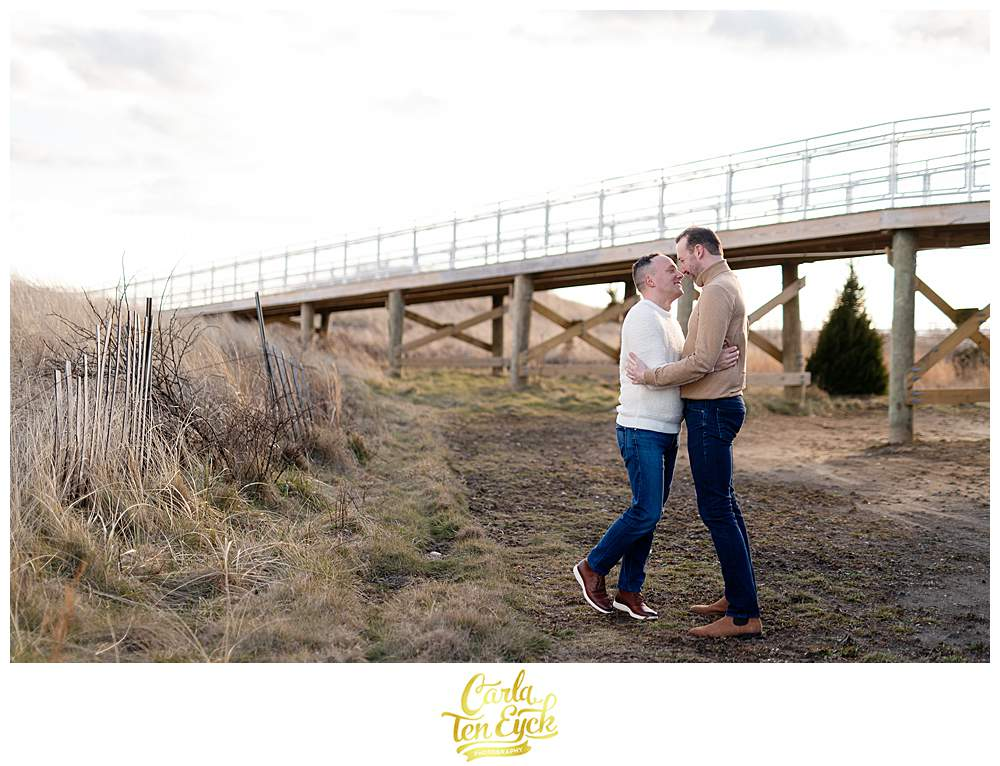 Two grooms during their winter engagement session at Silver Sands beach in Milford CT