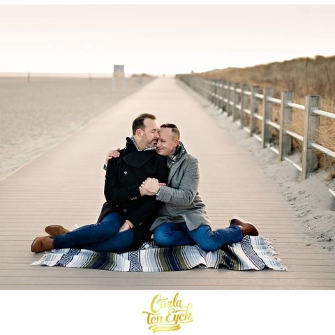 Two grooms cuddle during their engagement session at Silver Sands Beach in Milford CT