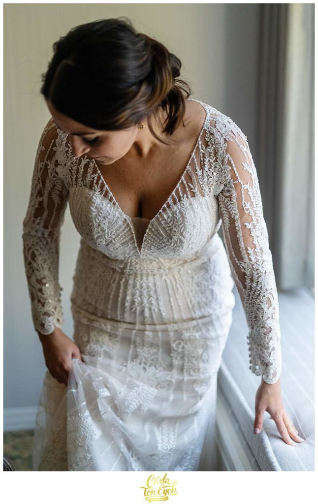 A bride puts on her wedding gown by Pronovias at her wedding in Irvington NY