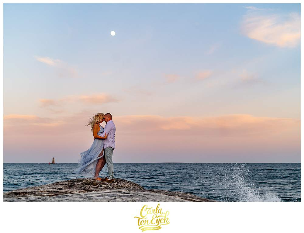 A couple poses on the rocks of Great Island Common in Portsmouth New Hampshire during their engagement session