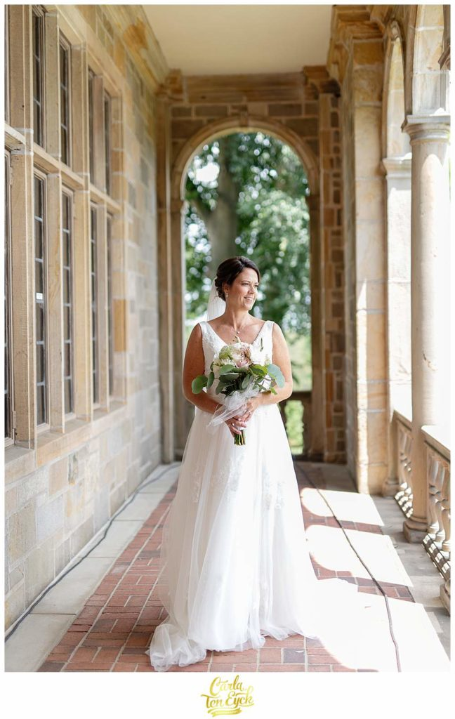 A bride stands in the light during her Fairfield University wedding in Fairfield CT