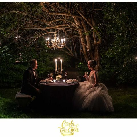 A bride and groom dine by candlelight at their Lord Thompson Manor wedding in Thompson CT