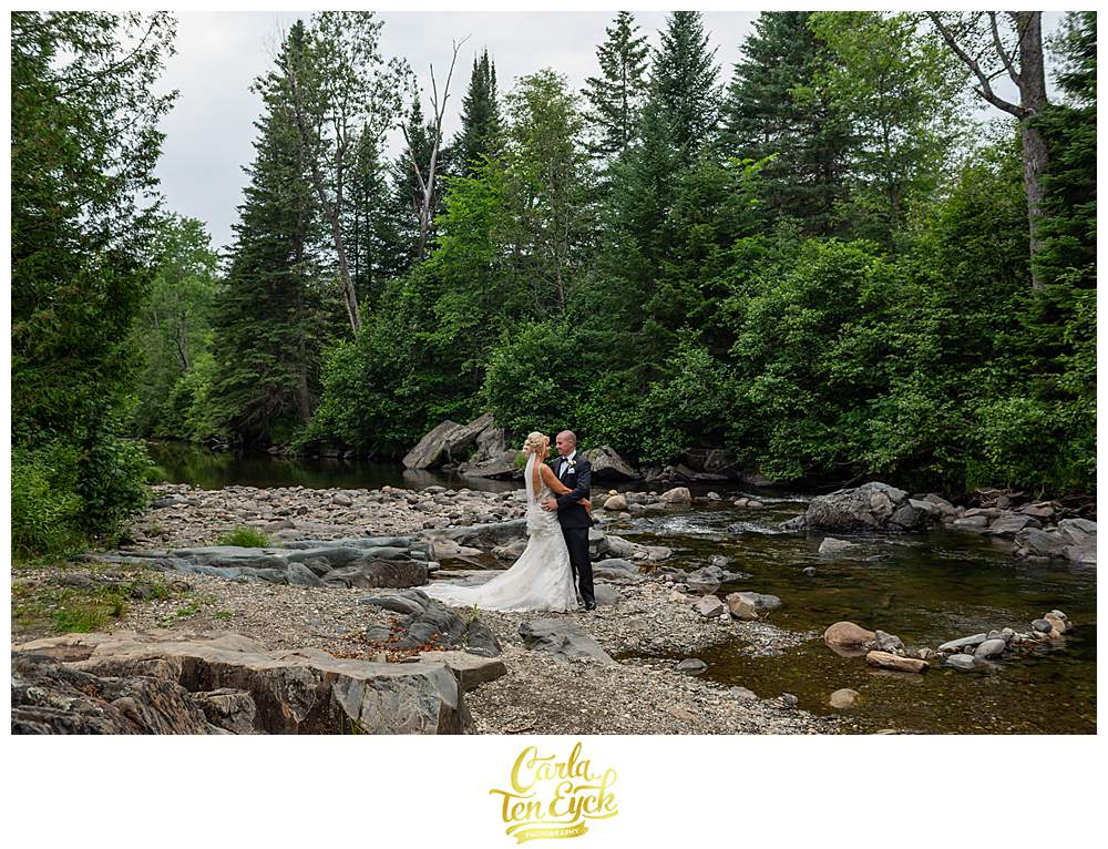 A couple poses for photos in a stream during their New Hampshire wedding.