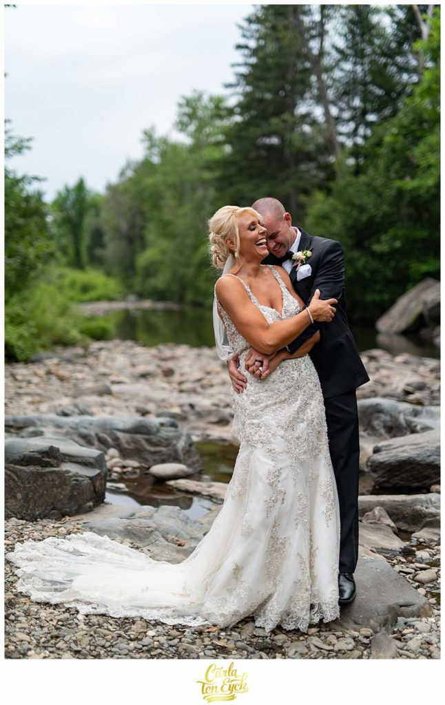 A couple laughs in a stream during their New Hampshire wedding