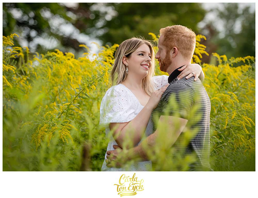 A couple snuggles in the goldenrod during their Harkness Park engagement session in Waterford CT