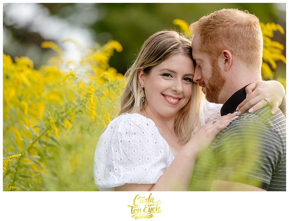 A couple kisses in the goldenrod at Harkness Park in Waterford CT during their engagement session
