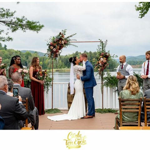 A bride kisses her new husband at their Camp Lenox summer camp wedding in Otis MA